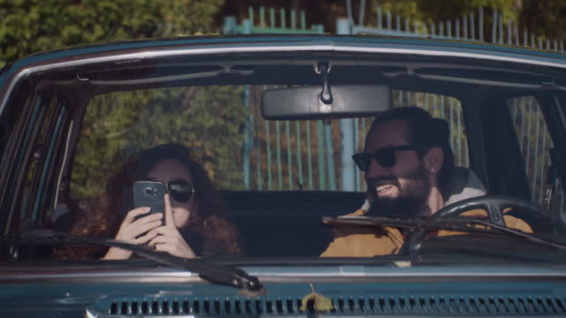 Young loving couple sitting in a retro car video