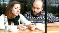 Young loving couple taking selfie in a café video