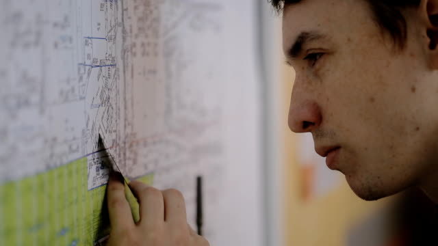 Young male architect working at stand plan with a ruler and pen, measuring distance on plan video