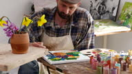 4К Young male artist painting in workshop video