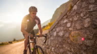 Young male athlete cycling on a mountain pass at sunset video