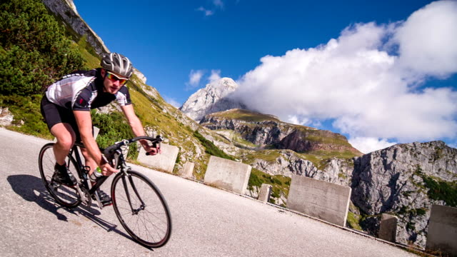 Young male athlete cycling on a mountain pass video