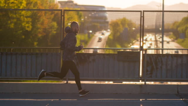 Young male athlete running on a bridge above traffic video