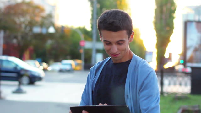 Young male browsing tablet pc computer smiling at camera outdoor video