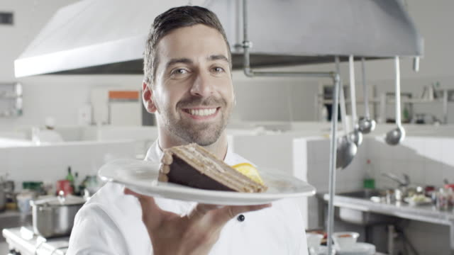 Young male chef showing cake video