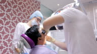 Young male dentist treats patient's teeth using dental unit under supervision of a nurse video