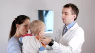 A young male doctor gives a play to a child with a stethoscope. The boy is in his mother's arms video