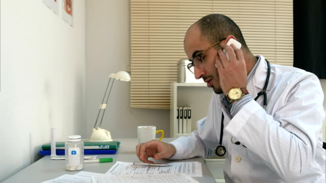 Young male doctor in glasses taking a phone call video