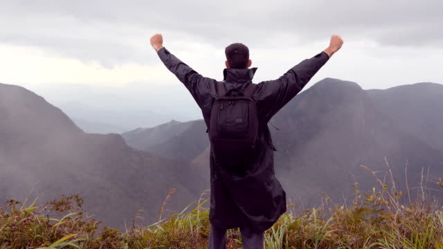 Young male hiker in raincoat with backpack reaching up top of mountain and raised hands. Man tourist standing on the edge of beautiful canyon, victoriously outstretching arms up. Rear back view video