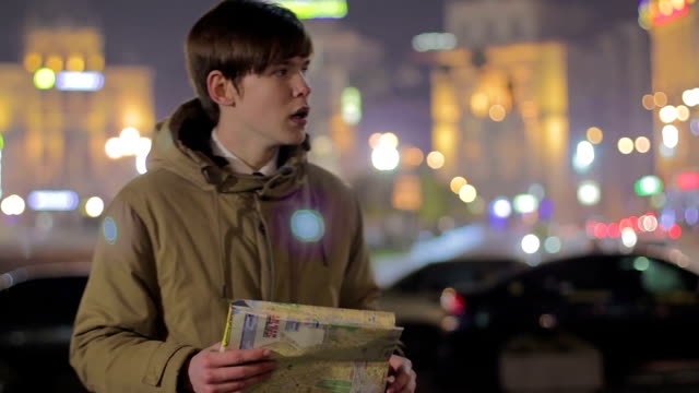 Young male looking at map and asking passerby to help find the way, tourism video