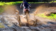 Young male motocross rider driving through a puddle of mud video
