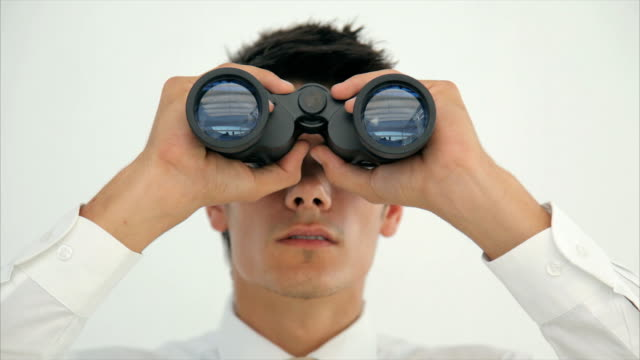Young male professional looking through binoculars in office video