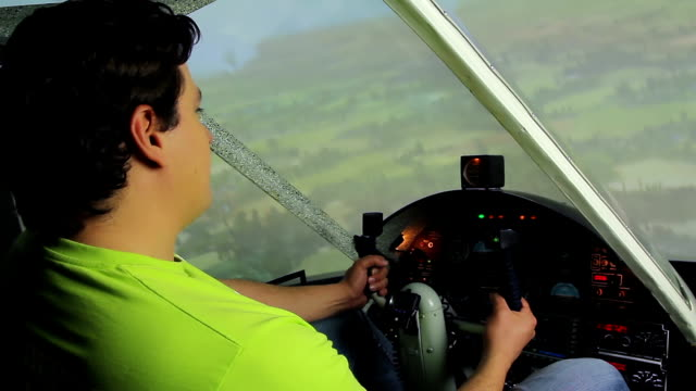 Young male sitting in cockpit, enjoying flight in plane simulator, hobby video