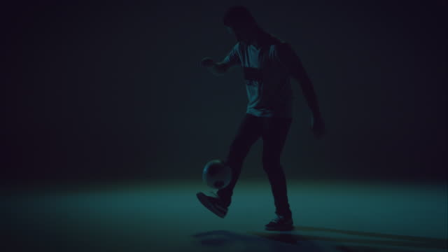 young male soccer freestyler is doing kick-ups. video