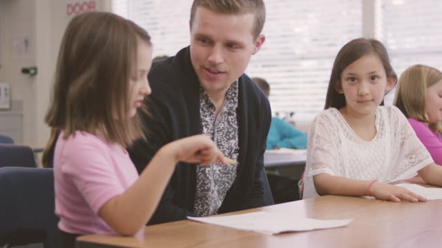 Young male teacher working with elementary aged students in classroom video