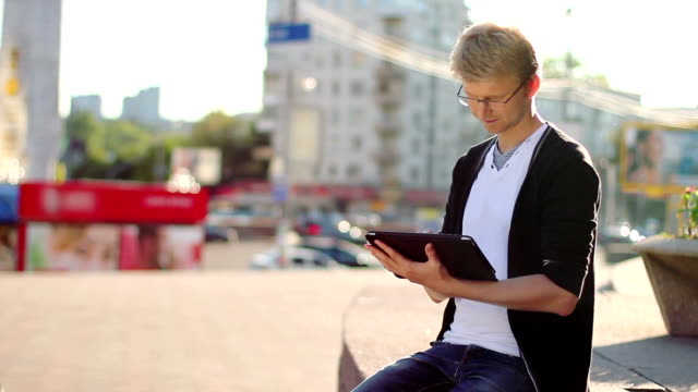 Young male with tablet pc pad smiles reads device video