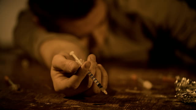 Young man addicted to drugs dying at hideout with syringe in hand after overdose video