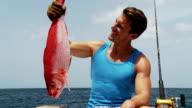 Young man admires his fish video