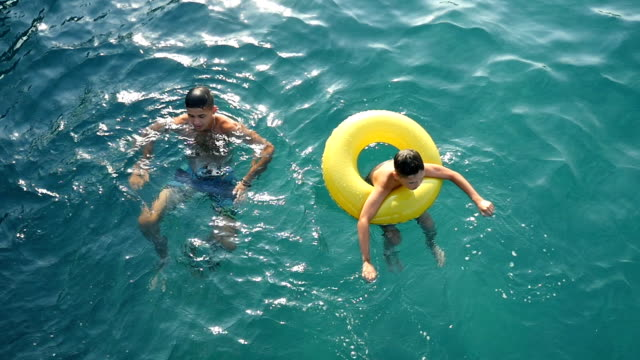 Young man and a boy in an inflatable ring swim in the blue sea waters in slo-mo video