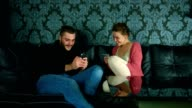 Young man and a woman sitting on a couch in the living room and playing games on their smart phones together video