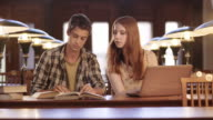 DS Young man and woman studying in library video