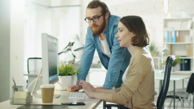 Young Man and Beautiful Woman Discuss Working Issues at Workplace. She Sits at the Table. He Stands Beside Her. They  Talk and Point at Something on the Screen. video