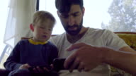 Young man and little boy look at a cell phone together video