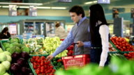 Young man and woman buying vegetable video