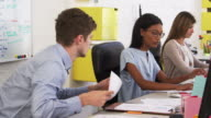Young man and woman discussing document in open plan office video
