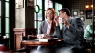 Young man and woman flirting in cafe and drinking coffee. video