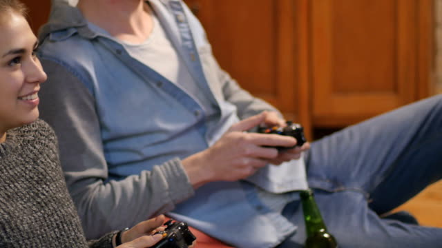 Young man and woman playing on the joysticks video