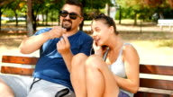 Young man and woman sitting on a bench in the park and listening to music played from a smart phone video