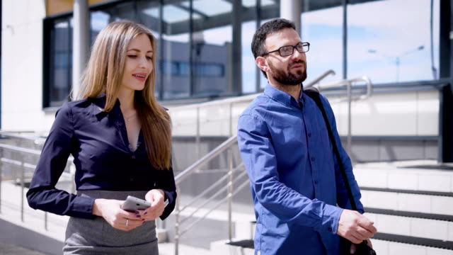 Young man and woman walking together outside. Handsome fellow taking a walk with his beautiful colleague. Elegant lady in smart suit is holding smartphone and speaking to her friend video
