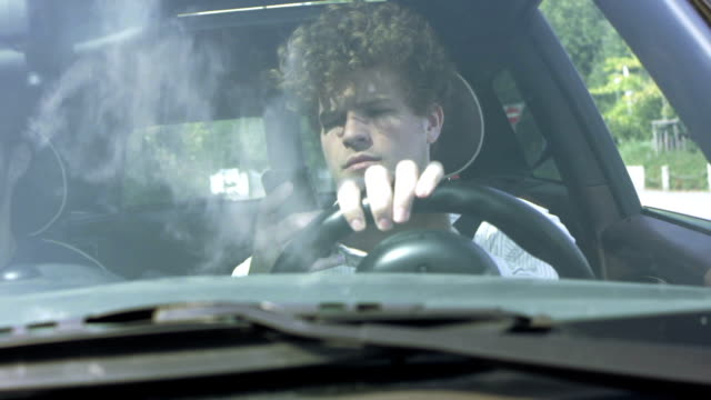 Young man answers his phone while driving video