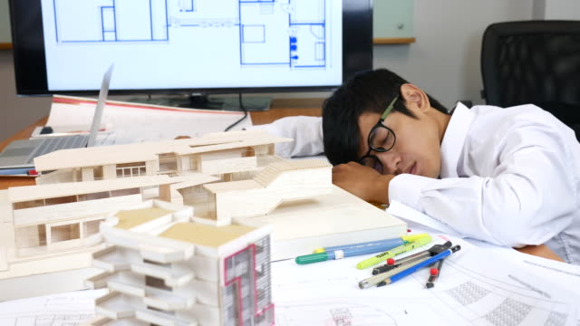 Young man architect sleeping on his Artificial model and blueprints video