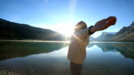 Young man arms outstretched by the lake at sunrise video