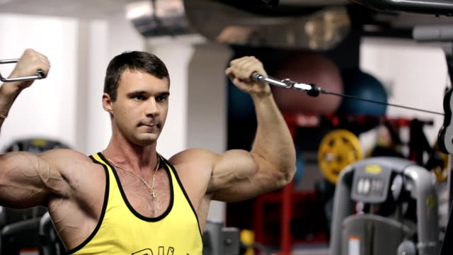 Young man at the gym trains his huge arm muscles video