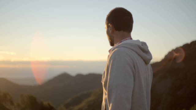 Young man back view on mountain outdoor look at sun at sunrise sunset - HD video footage video