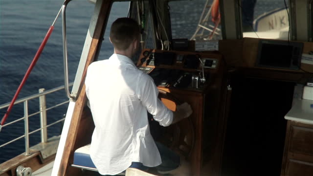 Young Man Behind The Wheel Of A Boat video