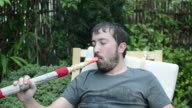 Young man blowing smoking water pipe and drinking tea video