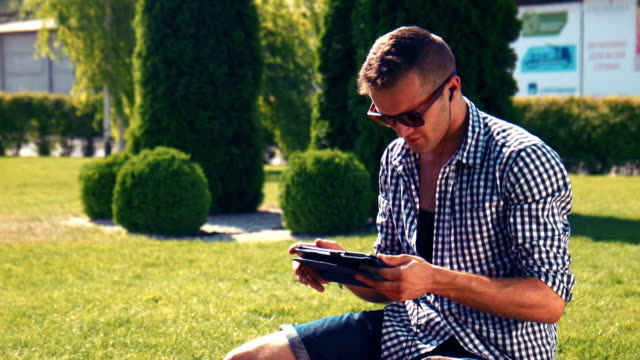 Young man browsing the internet on a tablet video