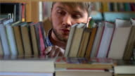 Young man browsing through the racks of books in a library video