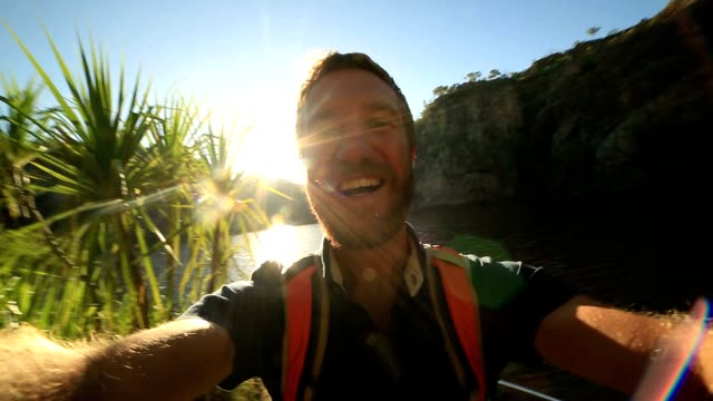 Young man by the lake takes a selfie portrait video