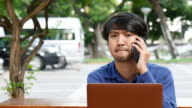 Young Man Calling on Phone with Laptop video