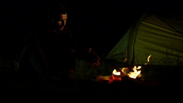 Young man camping at night on mountain video HD video
