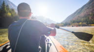 Young man canoeing on a lake at the mountainside video