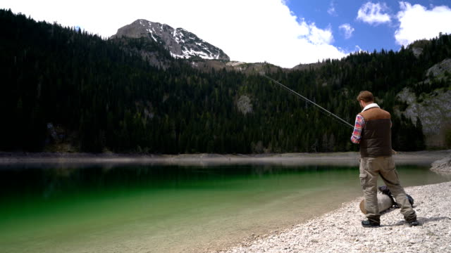 young man cast a spinning on the shores of scenic Lake video