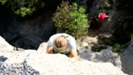 Young man climbs steep rock wall above belayer video