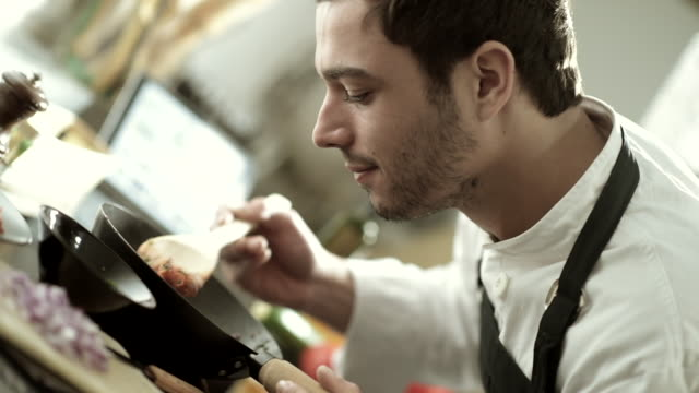 Young man cooking in kitchen at home video