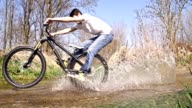 SLO MO Young man cycling through a puddle video